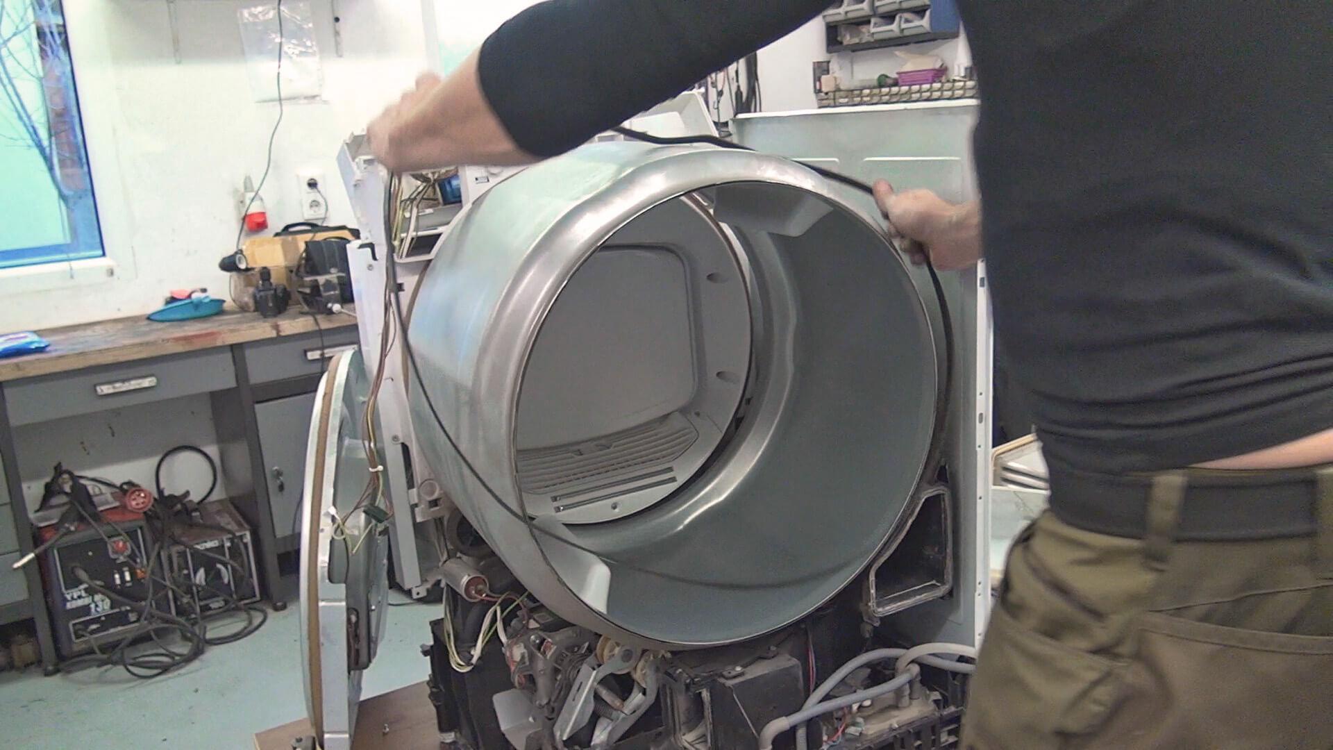 Neuen Antriebsriemen über die Trommel schieben